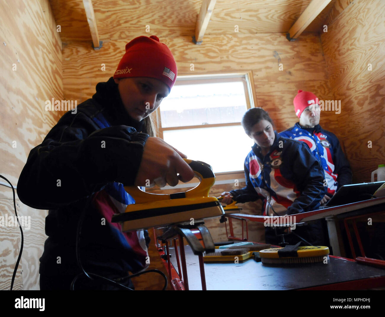 Spc. Lisa Roberts, a member of the Ohio National Guard, waxes her skis in preparation for her next race at Camp Ethan Allen Training Site, Jericho, Vt., March 4, 2017. Over 120 athletes from 23 different states are participating in the 2017 National Guard Bureau Biathlon Championships. (U.S. Army National Guard photo by 1st Lt. Aaron Smith) - Stock Image
