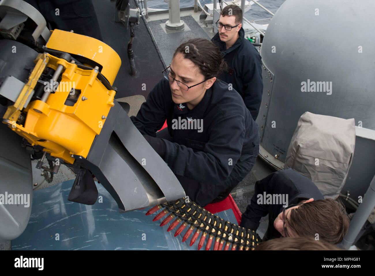170314-N-NB544-145  PHILIPPINE SEA (March 14, 2017) Fire Controlman 3rd Class Alexandria Ricalde loads Mark 244 20 mm rounds into a Close-In Weapons System during an ammo upload exercise aboard the amphibious assault ship USS Bonhomme Richard (LHD 6). The ship and its expeditionary strike group are on a routine patrol operating in the Indo-Asia-Pacific region to enhance warfighting readiness and posture forward as a ready-response force for any type of contingency. (U.S. Navy photo by Mass Communication Specialist 2nd Class Kyle Carlstrom/Released) - Stock Image