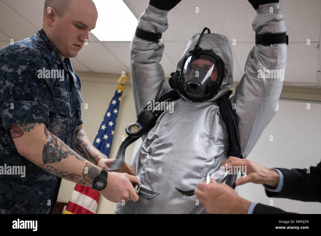 170308-N-PO203-139 GROTON, Conn. (Mar. 8, 2017) Machinist's Mate nuclear 2nd Class Nicholas Lewis from the Los Angeles class-attack submarine USS Toledo (SSN 769), helps Machinist's Mate nuclear 2nd Class Cameron Sebastian don a prototype submarine steam suit ensemble during an orientation class held at Naval Submarine Base New London. The Navy Sea Systems Command (NAVSEA) via the Office of Naval Research (ONR) TechSolutions Office has funded the Navy Clothing and Textile Research Facility (NCTRF) to develop the next generation of protective gear for emergency responders to steam line ruptures - Stock Image
