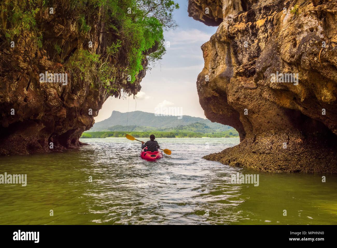 Kayaking under high cliffs in Thailand - Stock Image