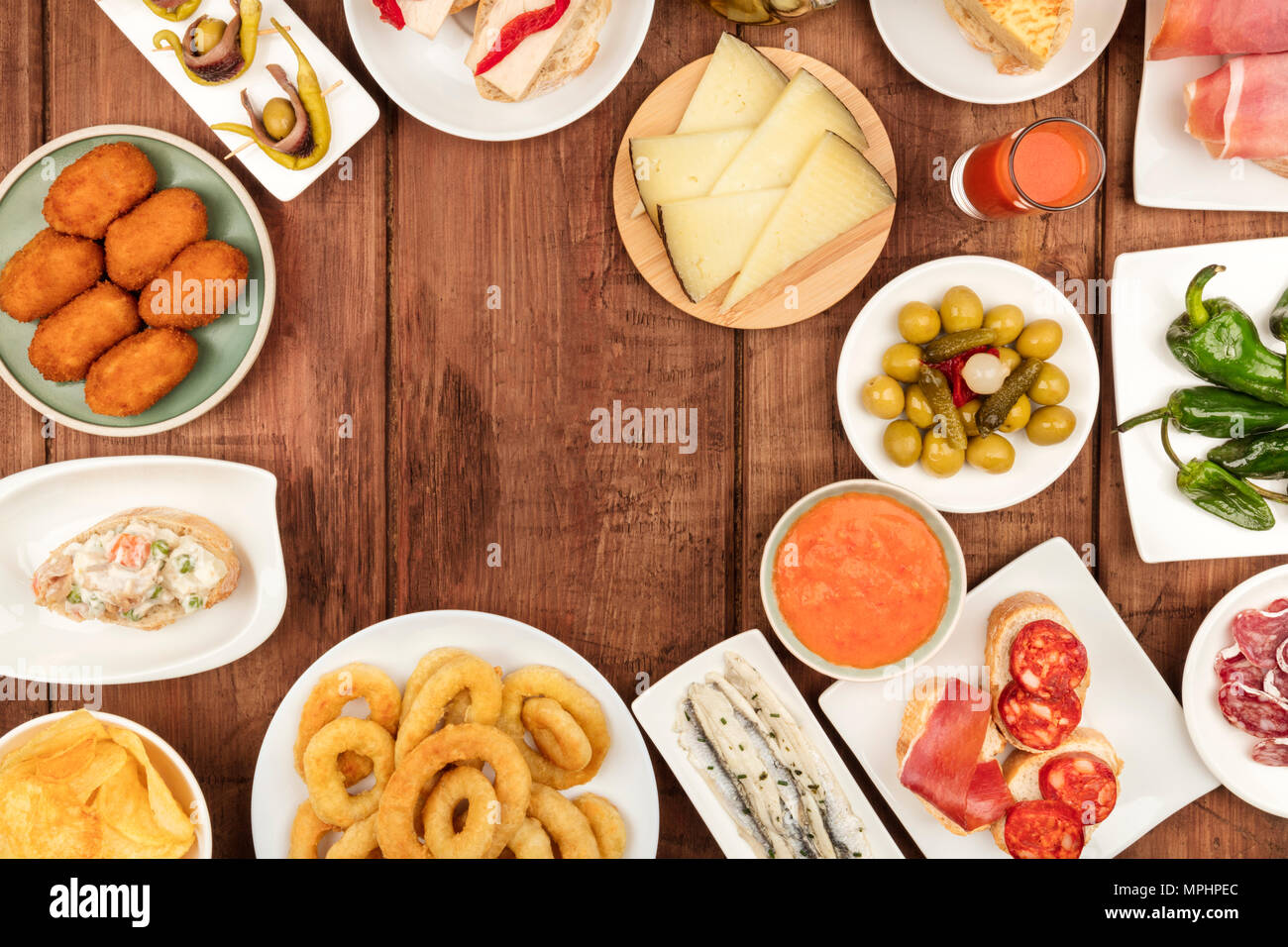 Food of Spain. An overhead photo of many different Spanish tapas, shot from above on a dark rustic texture. Gazpacho, cheese, olives, croquettes, boqu - Stock Image