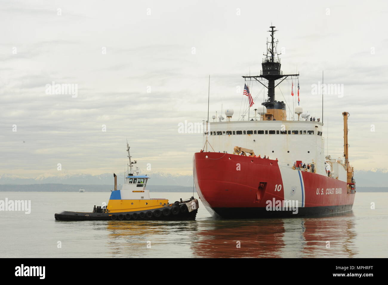The crew of the Coast Guard Cutter Polar Star, a 399-foot heavy icebreaker, is escorted by the crew of the Westrac II, a 73-foot towing vessel, as they moor to Pier 66 in Seattle, March 17, 2017.    The crew returned from a 107-day expedition to Antartica, which involved maintaining the decades-old icebreaker to ensure a year's worth of supplies and fuel safely reached the National Science Foundation's McMurdo and Amundsen-Scott South Pole stations.    U.S. Coast Guard photo by Petty Officer 3rd Class Amanda Norcross. - Stock Image