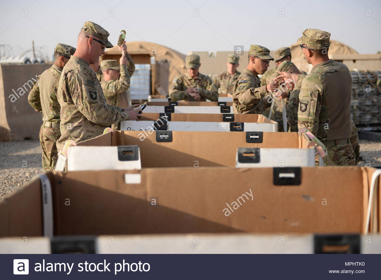 Soldiers from Task Force Forge prepare a shipment of supplies to send to an expeditionary advisory package near Bost airfield in Helmand Province, Afghanistan, March 7, 2017. The package is made up of about 20 advisers from the Army National Guard's 38th Infantry Division. (NATO photo by Kay M. Nissen) - Stock Image