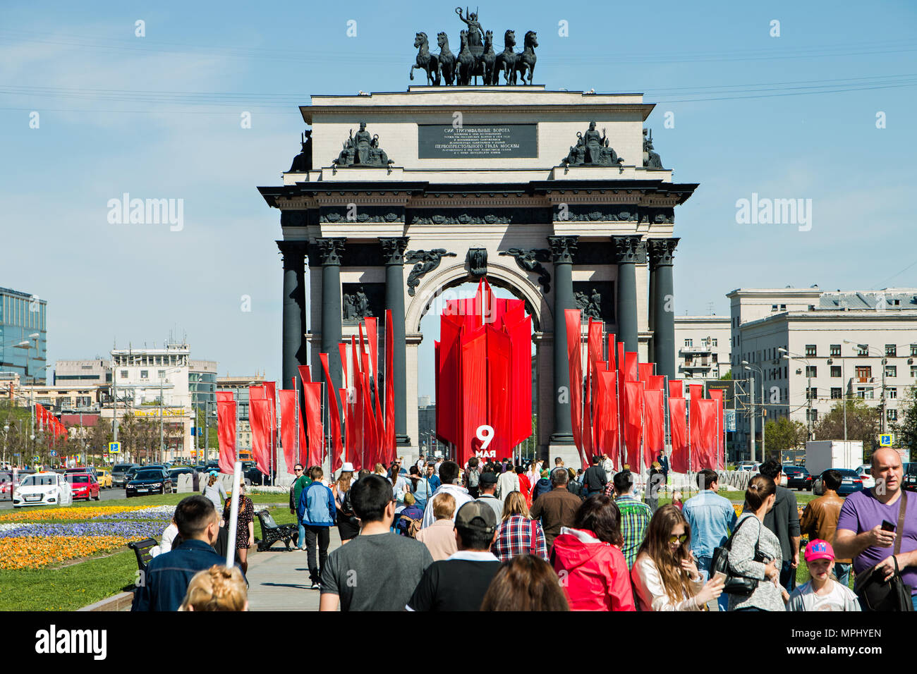 Moscow,Russia, May 9, 2018: The triumphal gate on Victory Day decorated with red flags and the crowd of people. - Stock Image