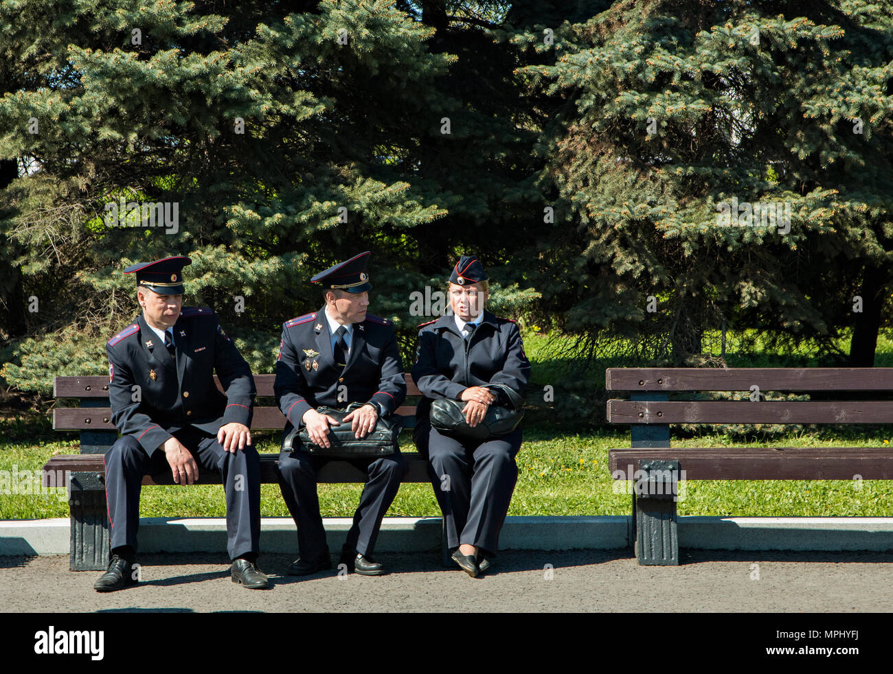 Moscow Russia, May 9, 2018: police officers sitting on a bench in sunny day - Stock Image