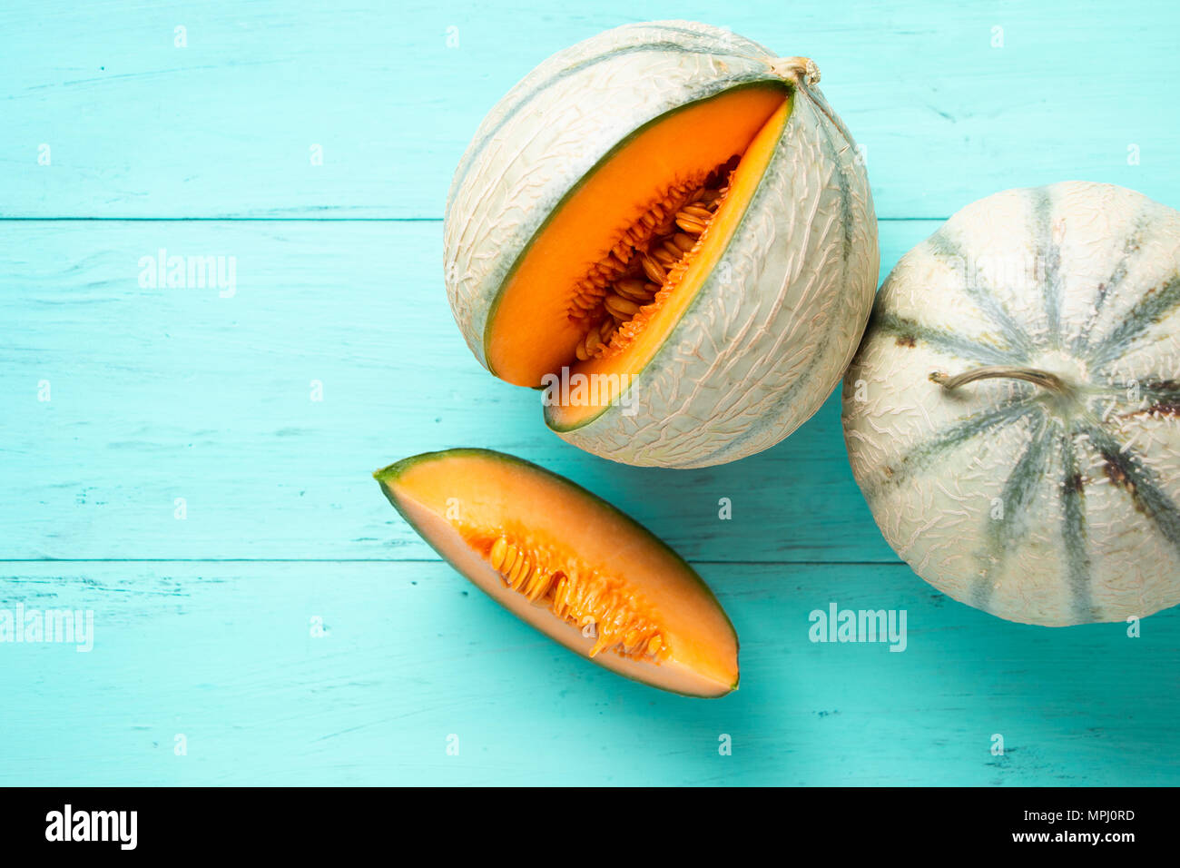 Two cantaloupe melons and one slice on an aquamarine wooden planks. Top view - Stock Image