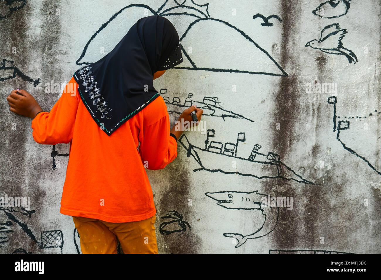 Krabi, Thailand - May 3, 2015: Muslim girl wearing black hijab drawing graphic image on wall of ruined house in Krabi, Thailand Stock Photo