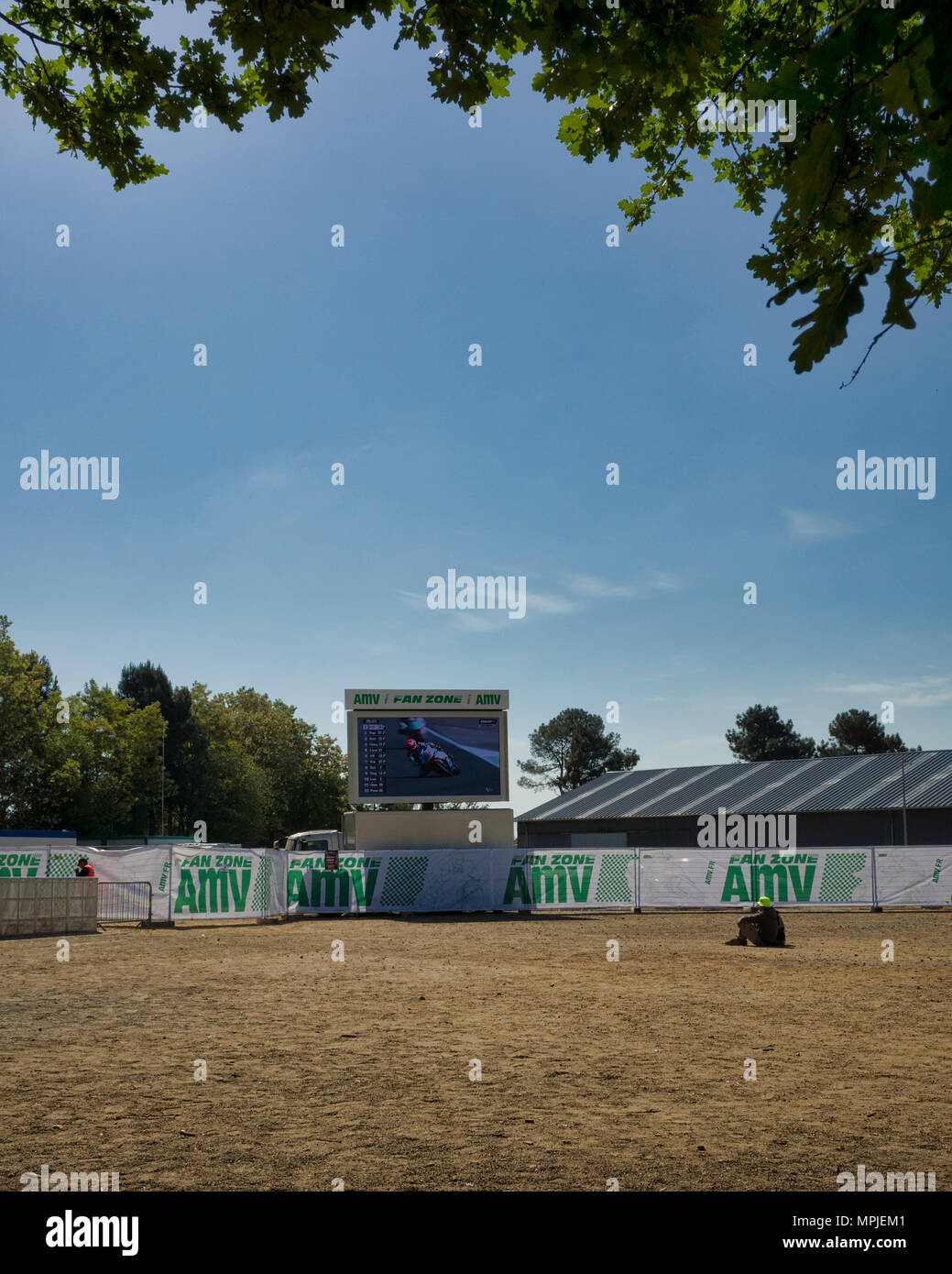 19-20th May 2018. Le Mans, France.  Behind the scenes at the MotoGP.  A young couple sit on the dirt ground to watch the practice sessions on one of the big screens.  The photograph is framed  with the leaves of an overhanging Oak tree. - Stock Image