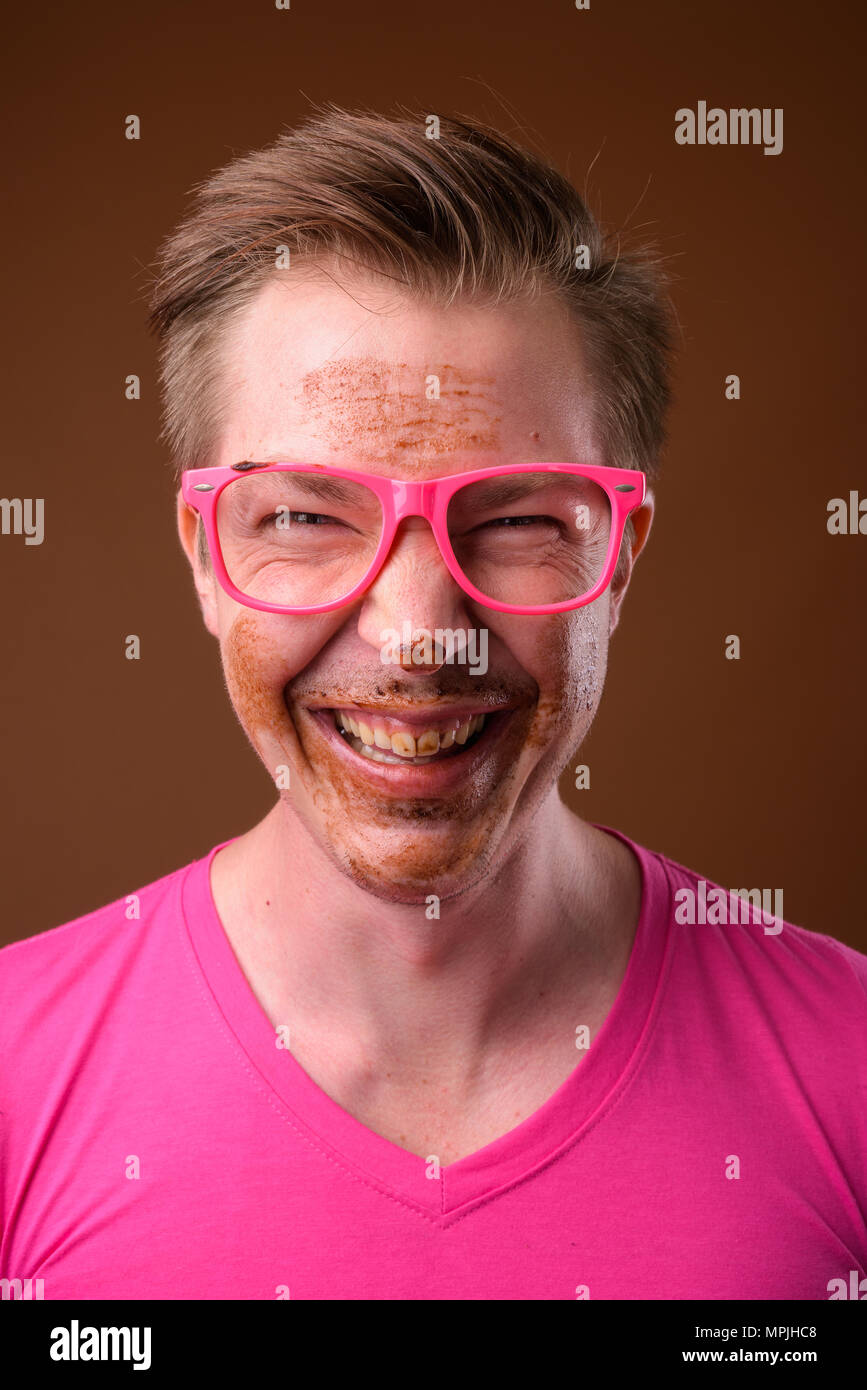 Young handsome man wearing pink shirt and eyeglasses against bro - Stock Image