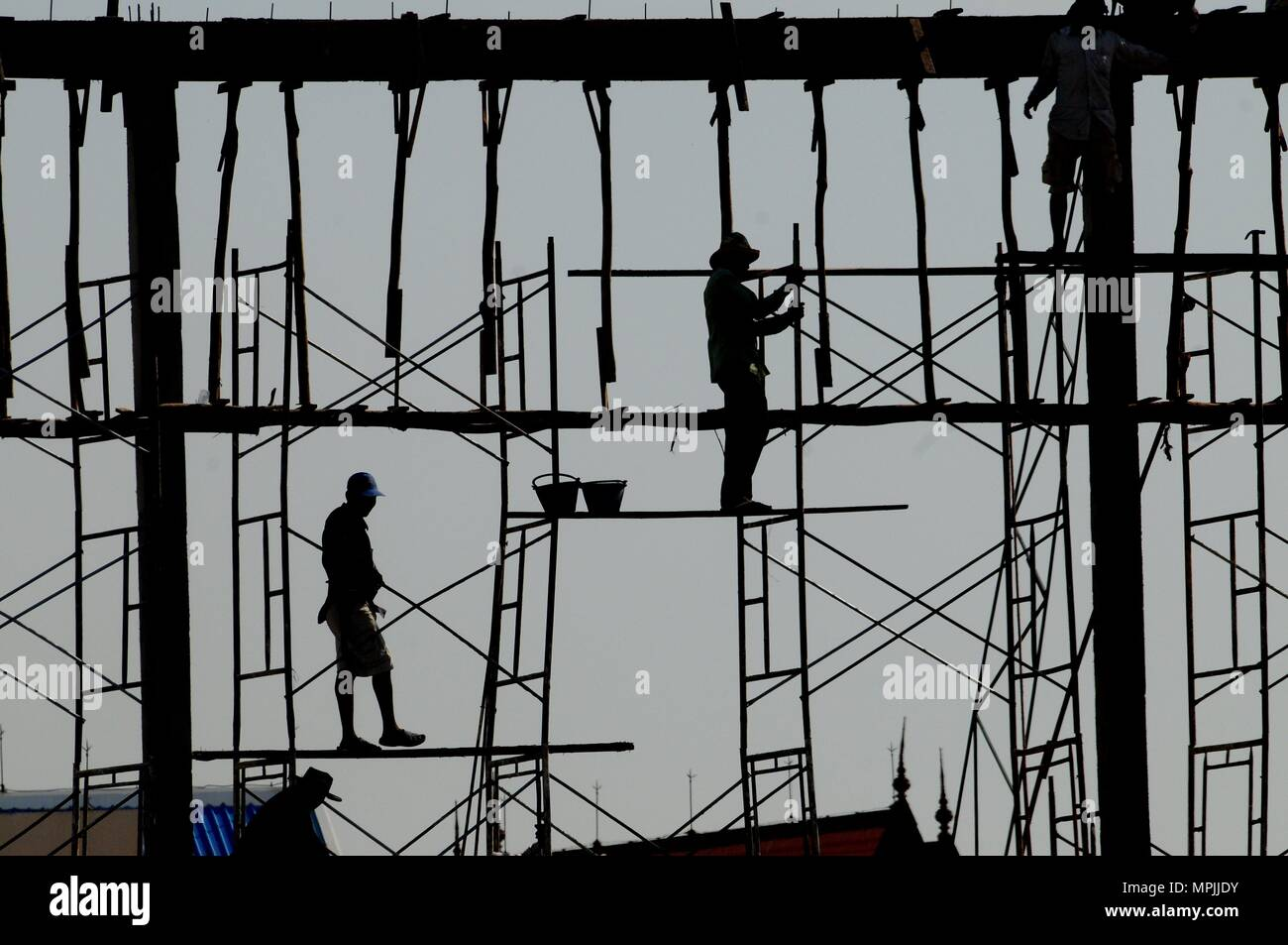 Silhouette of men working on a Bamboo Scaffolding, Phnom Penh, Cambodia - Stock Image