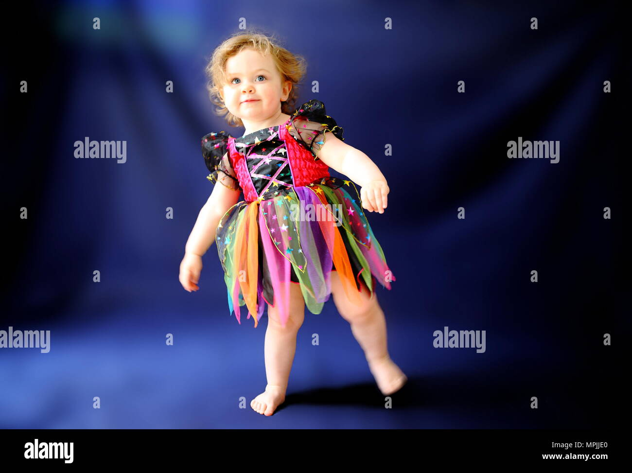 a young girl looks like a porcelain doll toy like dressed in halloween fairy dress on an inky blue background age 18 to 24 months june 2010 image by