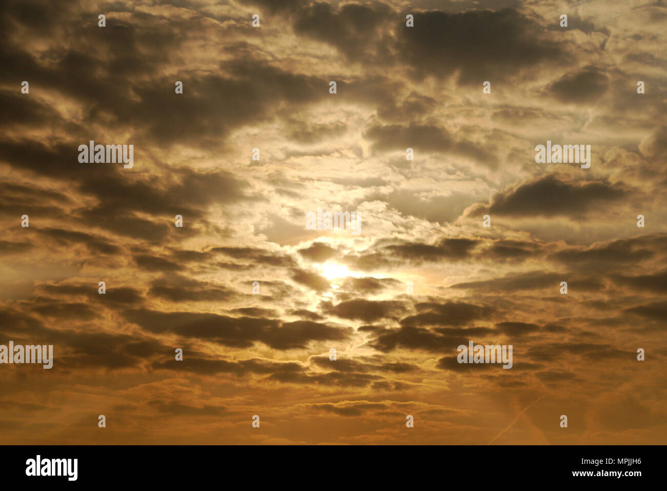 Evening sun partially obscured by clouds. Stock Photo