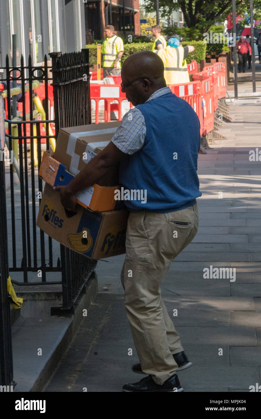 A man of Afro-Caribbean ethnicity carrying a pile of boxed and delivering packages to address in central London. Heavy lifting delivery man on rounds. - Stock Image