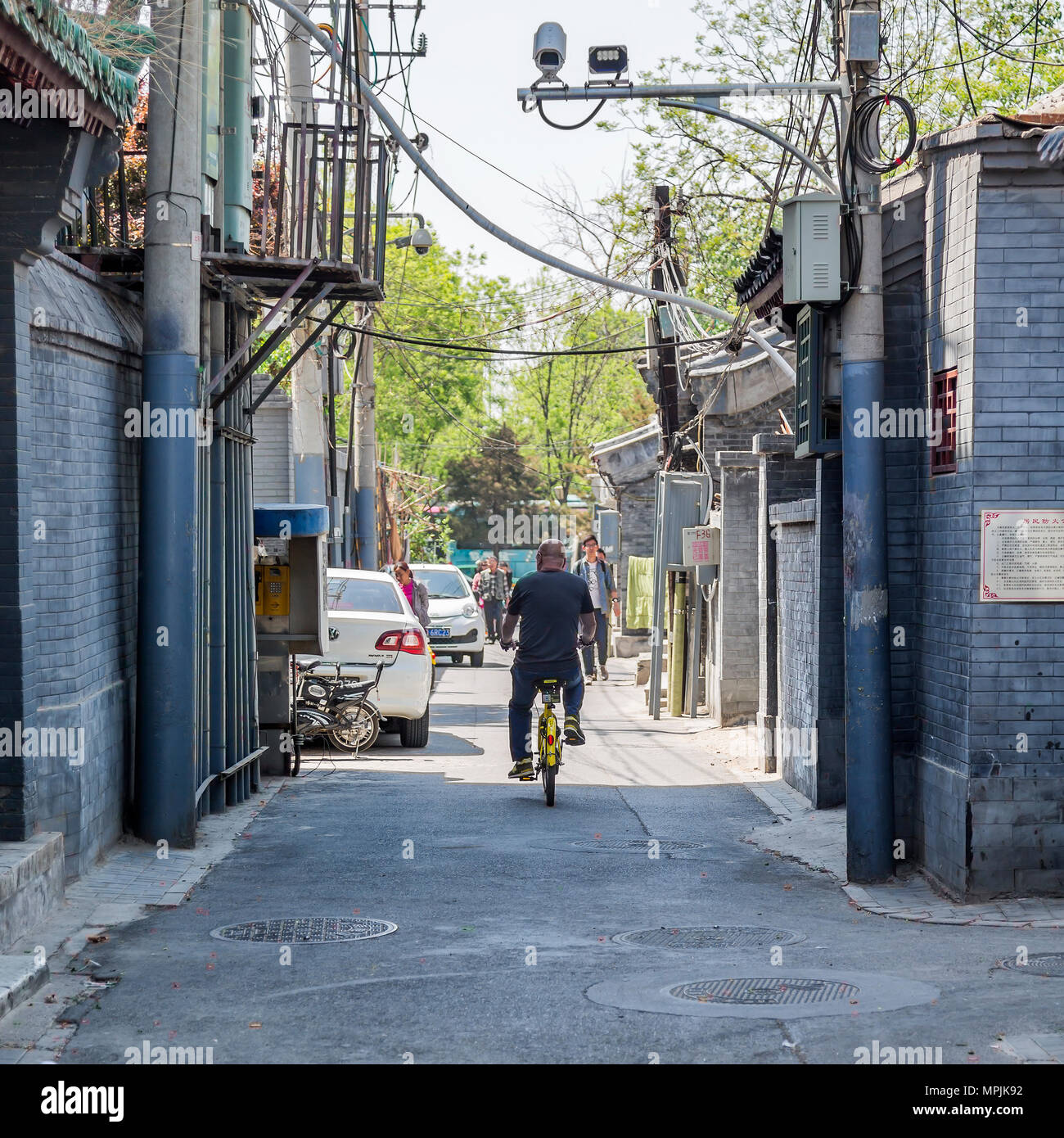 A Chinese man riding a bicycle on a backstreet in Beijing. Overlooked by a surveillance camera. - Stock Image
