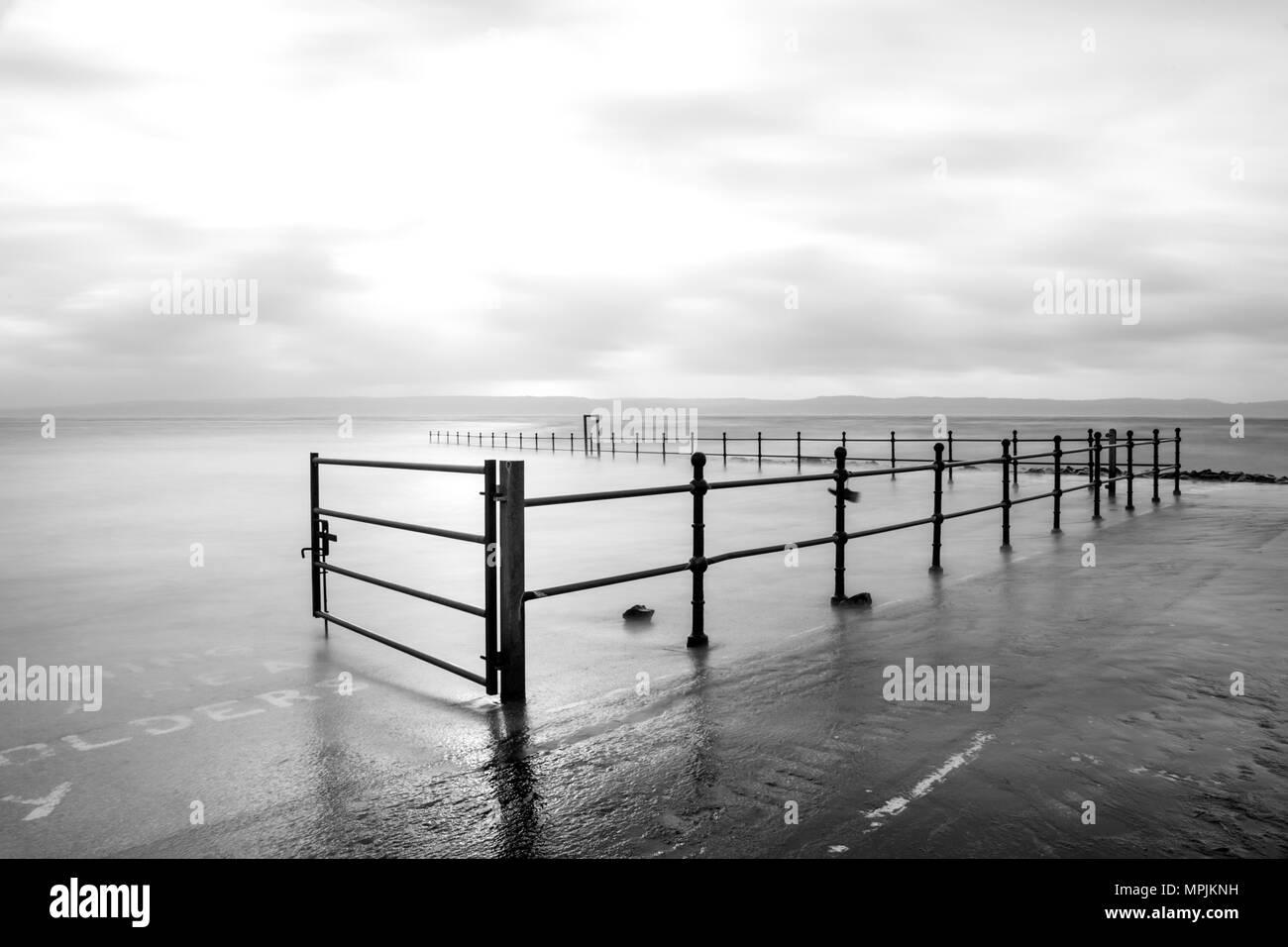 Marine lake wall with railings. Long exposure stormy sea. - Stock Image
