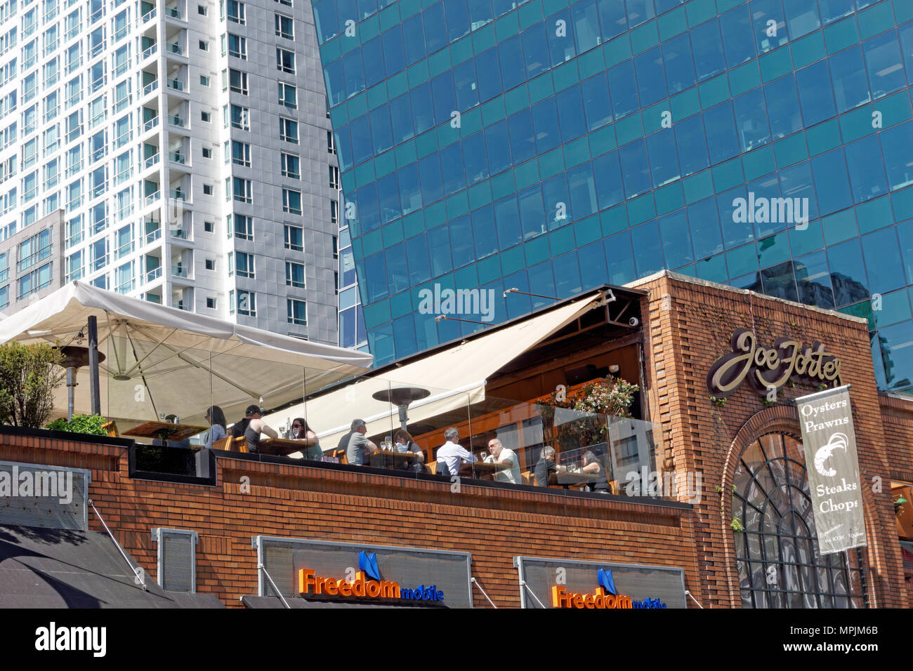 People dining on the rooftop patio of Joe Fortes steak and seafood restaurant on Thurlow Street in downtown  Vancouver, BC, Canada - Stock Image