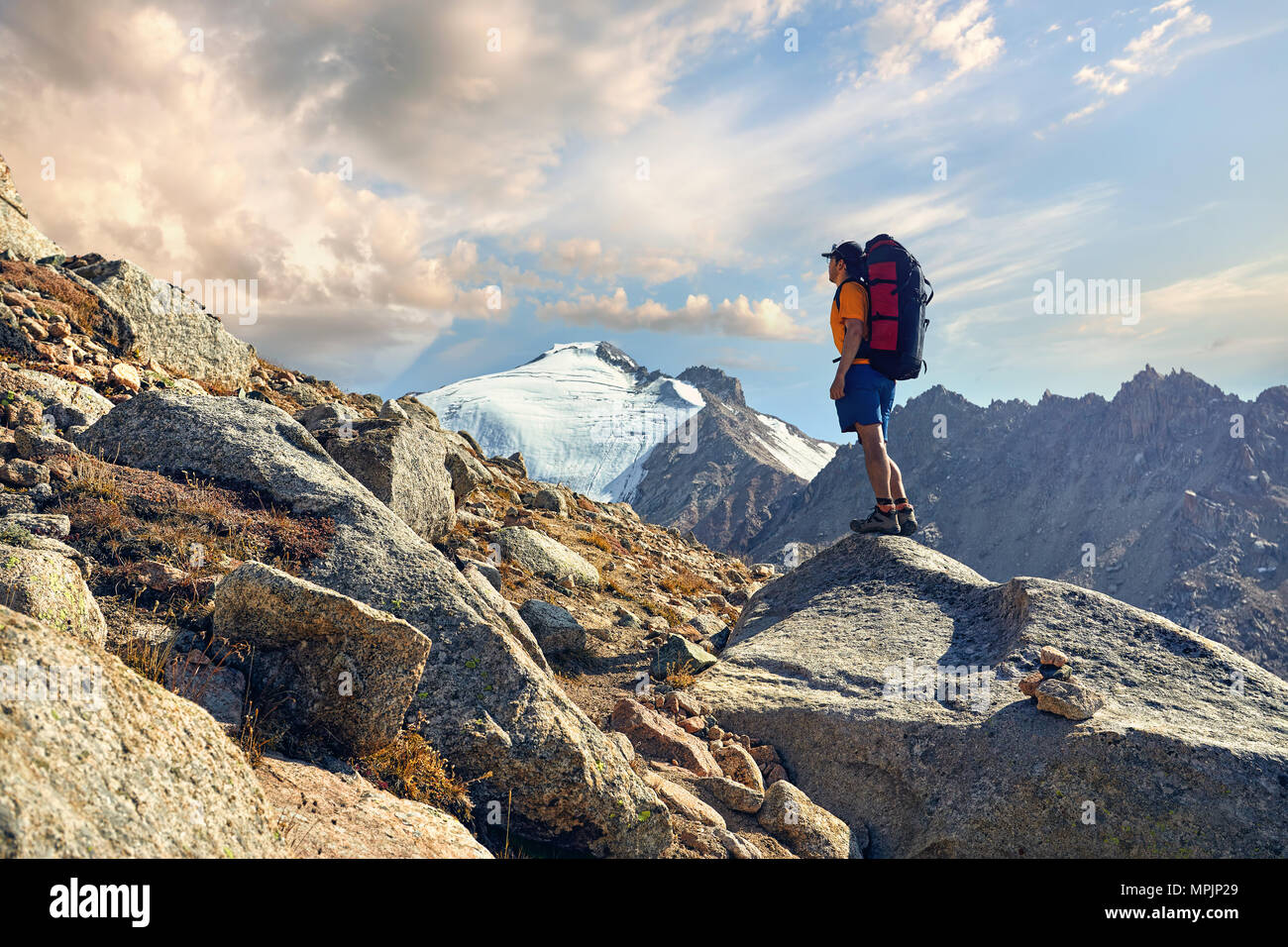 Hiker in orange shirt with big backpack looking on the snowy summit at background - Stock Image