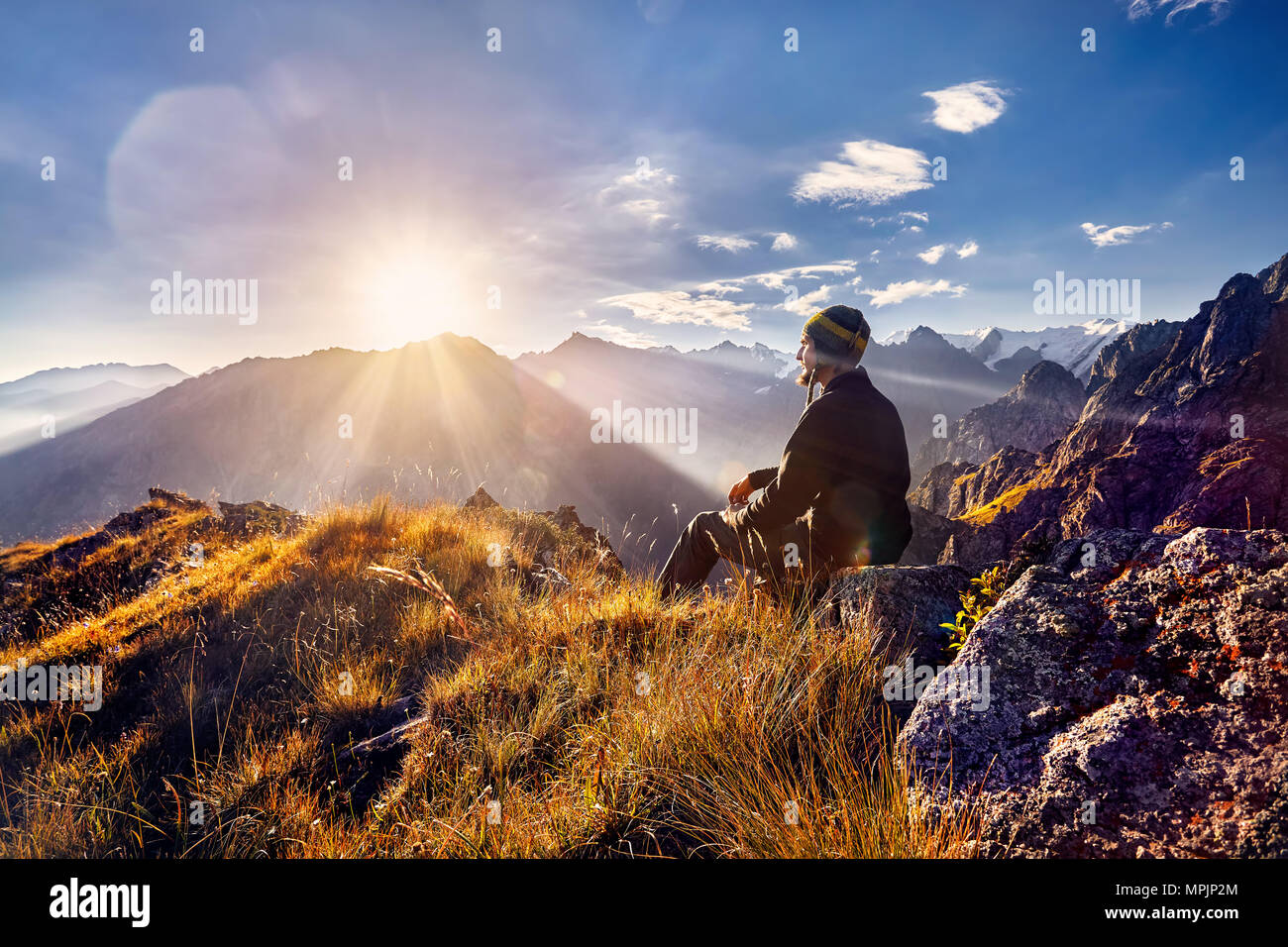 Tourist in Nepali hat sitting on the hill and looking at sunrise in the mountains - Stock Image