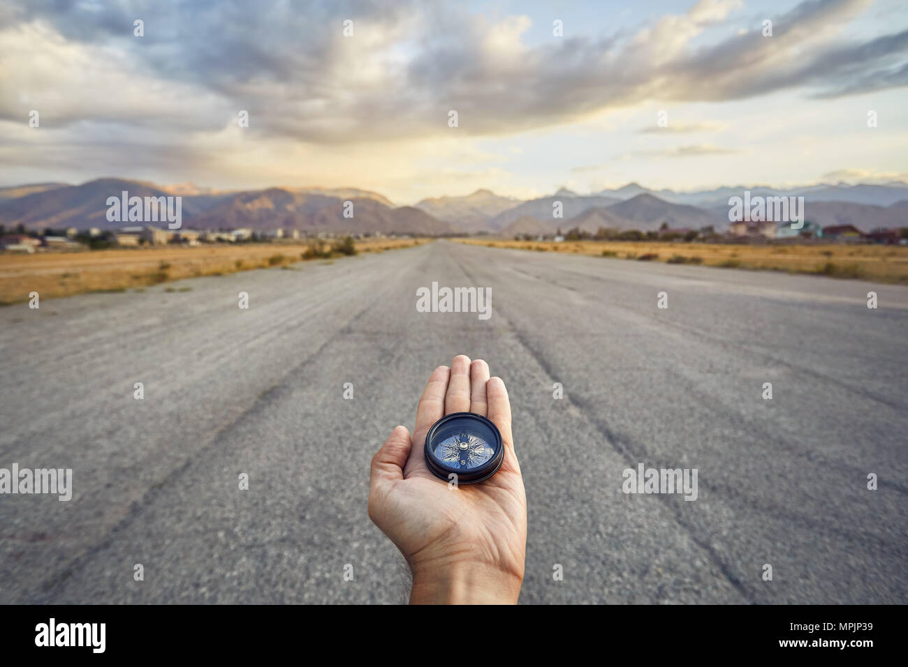 Traveler holding compass on the road with mountains at sunrise sky background. Travel and adventure concept. - Stock Image