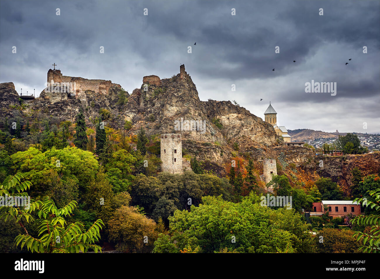 Old medieval castle Narikala at overcast cloudy sky at autumn time in Tbilisi, Georgia - Stock Image
