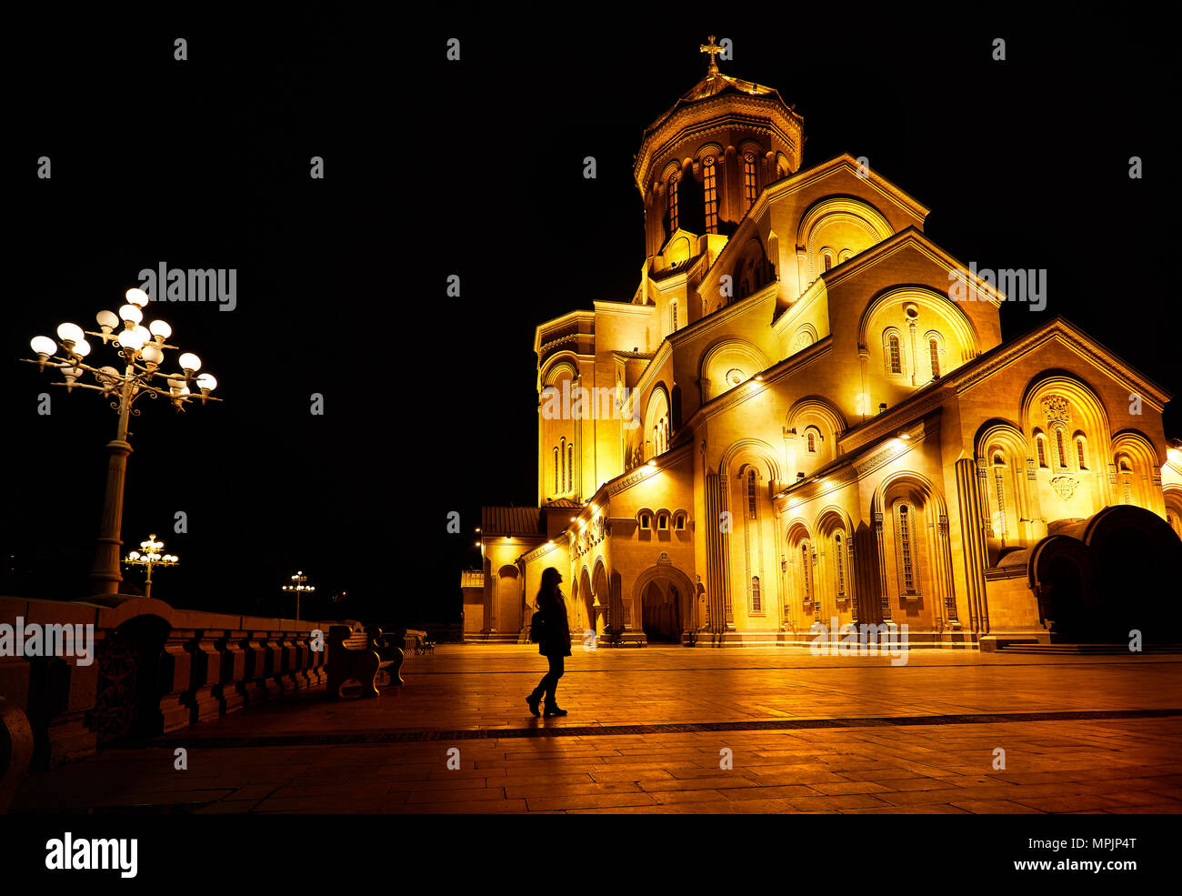 Woman silhouette near The Holy Trinity Cathedral or Tsminda Sameba Church at night in Tbilisi, Georgia - Stock Image