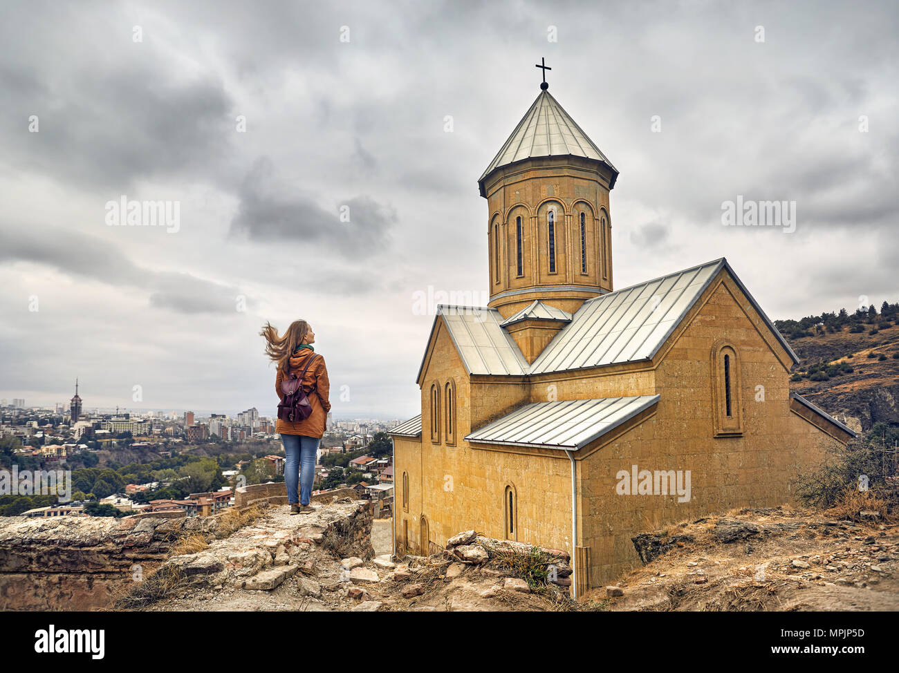 Tourist woman near Cathedral in Old medieval castle Narikala at overcast cloudy sky in Tbilisi, Georgia - Stock Image