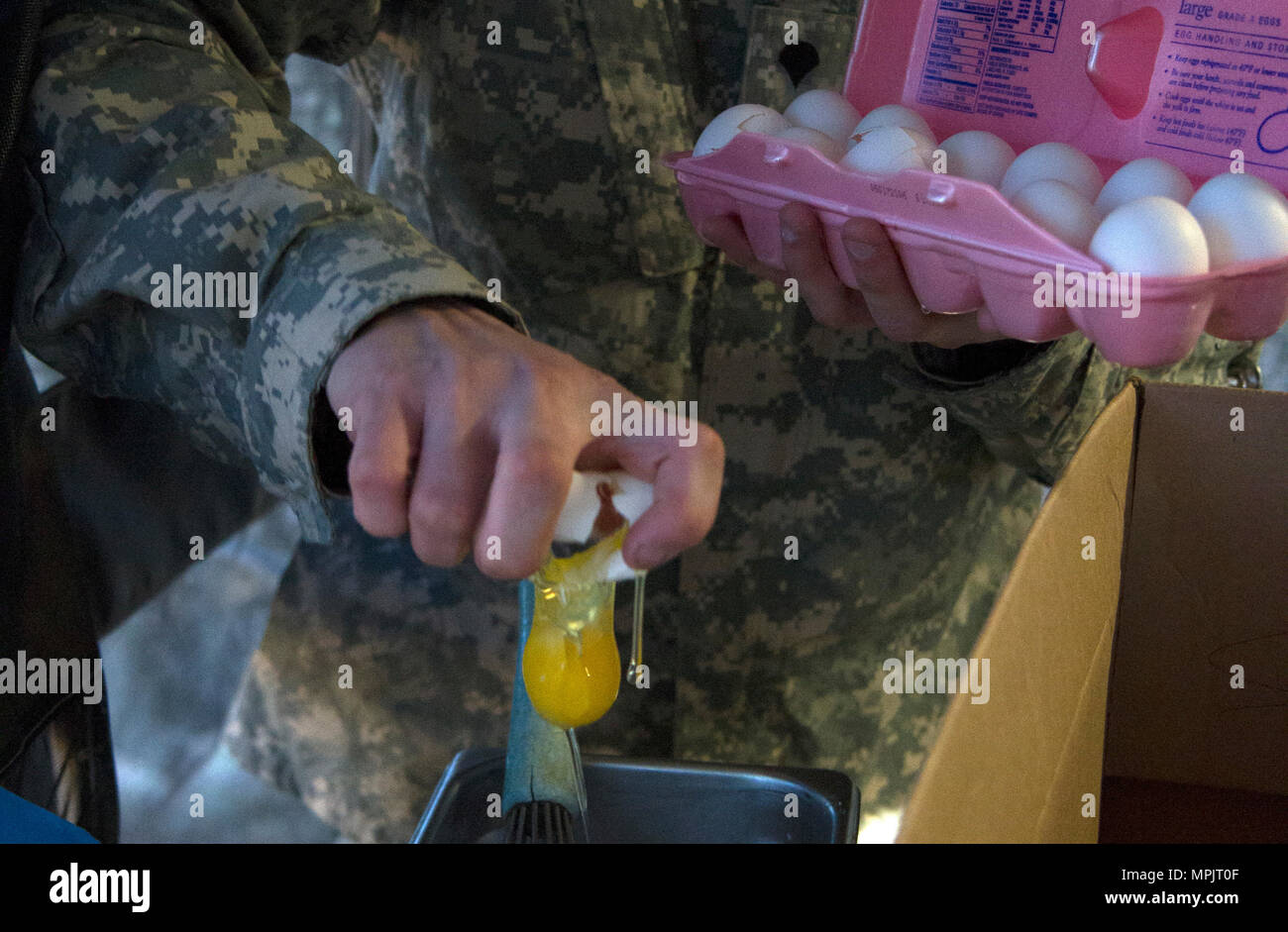 A U.S. Army Reserve Soldier from the culinary team of the 391st Military Police Battalion, breaks eggs in order to prepare crepes during food service operations in the field as part of the 49th Philip A. Connelly Award for Excellence in Army Food Service competition at Camp Blanding, Florida, March 17, 2017. The 391st MP Bn., one of four Army-wide finalists, selected Camp Blanding, Florida, as their location for the final level of testing in the competition. (U.S. Army Reserve photo by Sgt. 1st Class Carlos Lazo) - Stock Image