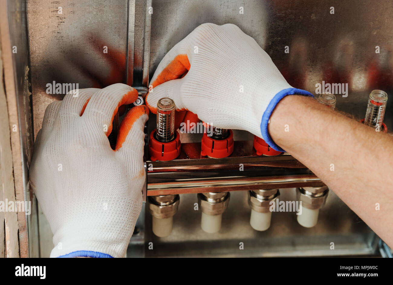 Installation of home heating. A worker fixes the underfloor heating manifold. Stock Photo