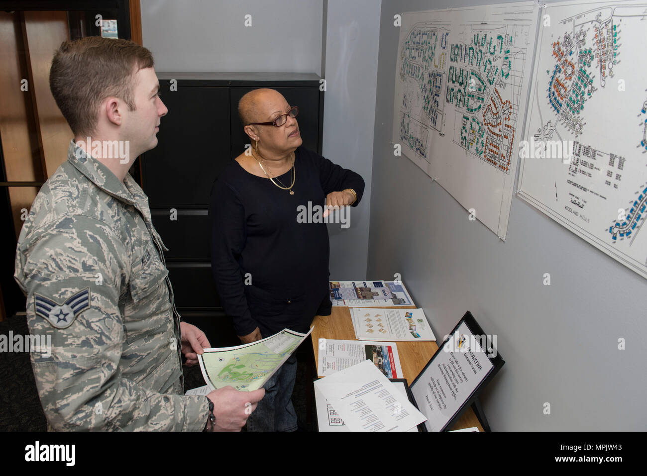 Karen Bryant, 88th Civil Engineering housing privatization manager, shows maps of base housing to Senior Airman Nathan Miller, 88th CE Emergency Management administrator technician, at Wright-Patterson Air Force Base, Ohio, March 15, 2017.  Wright-Patterson privatized housing provides affordable housing on and off base for active duty military service members relocating to a permanent change of station.  (U. S. Air Force photo by Michelle Gigante/Released) - Stock Image