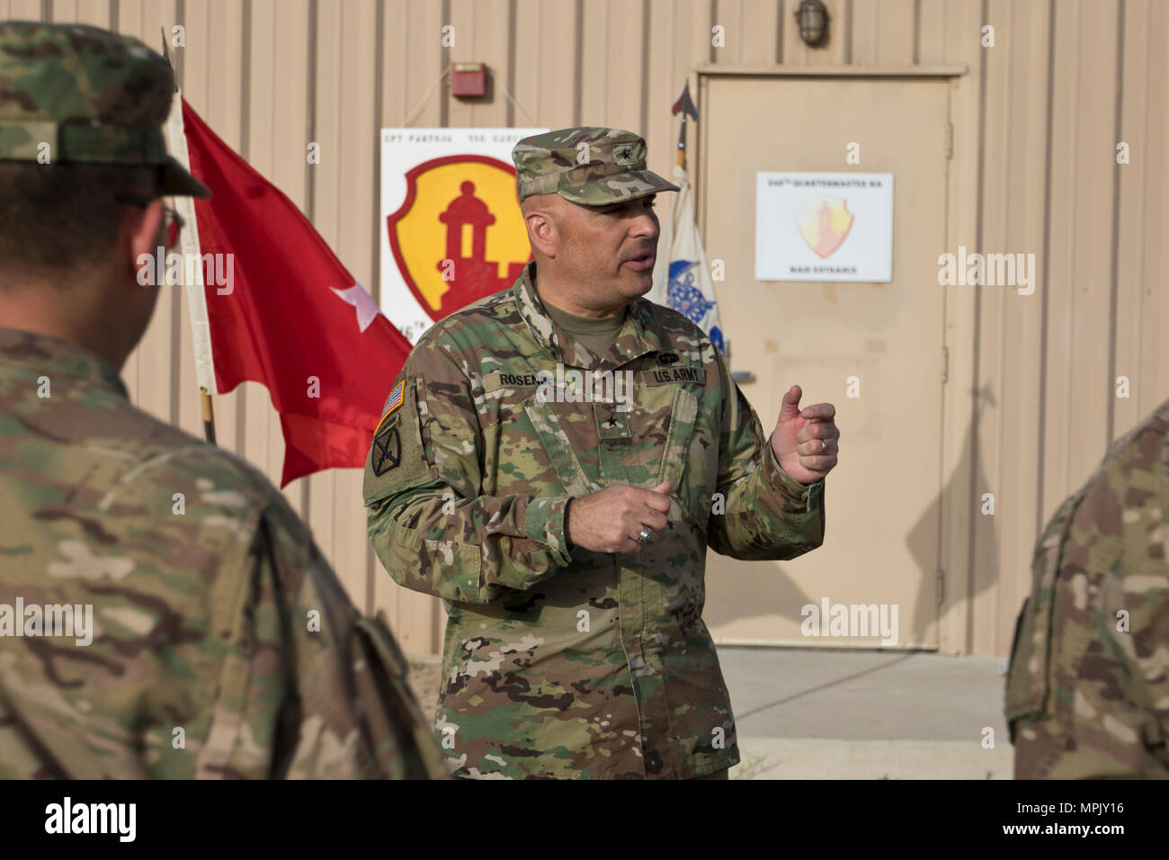 Brig. Gen. Alberto Rosende, commanding general of the 1st Mission Support Command, an Army Reserve unit based out of Fort Buchanan, Puerto Rico, talks about the importance of the combat shoulder sleeve insignia before a patching ceremony for the 246th Quartermaster Company (Mortuary Affairs) at Camp Arifjan, Kuwait, on Mar. 20, 2017. (U.S. Army photo by Staff Sgt. Dalton Smith) - Stock Image