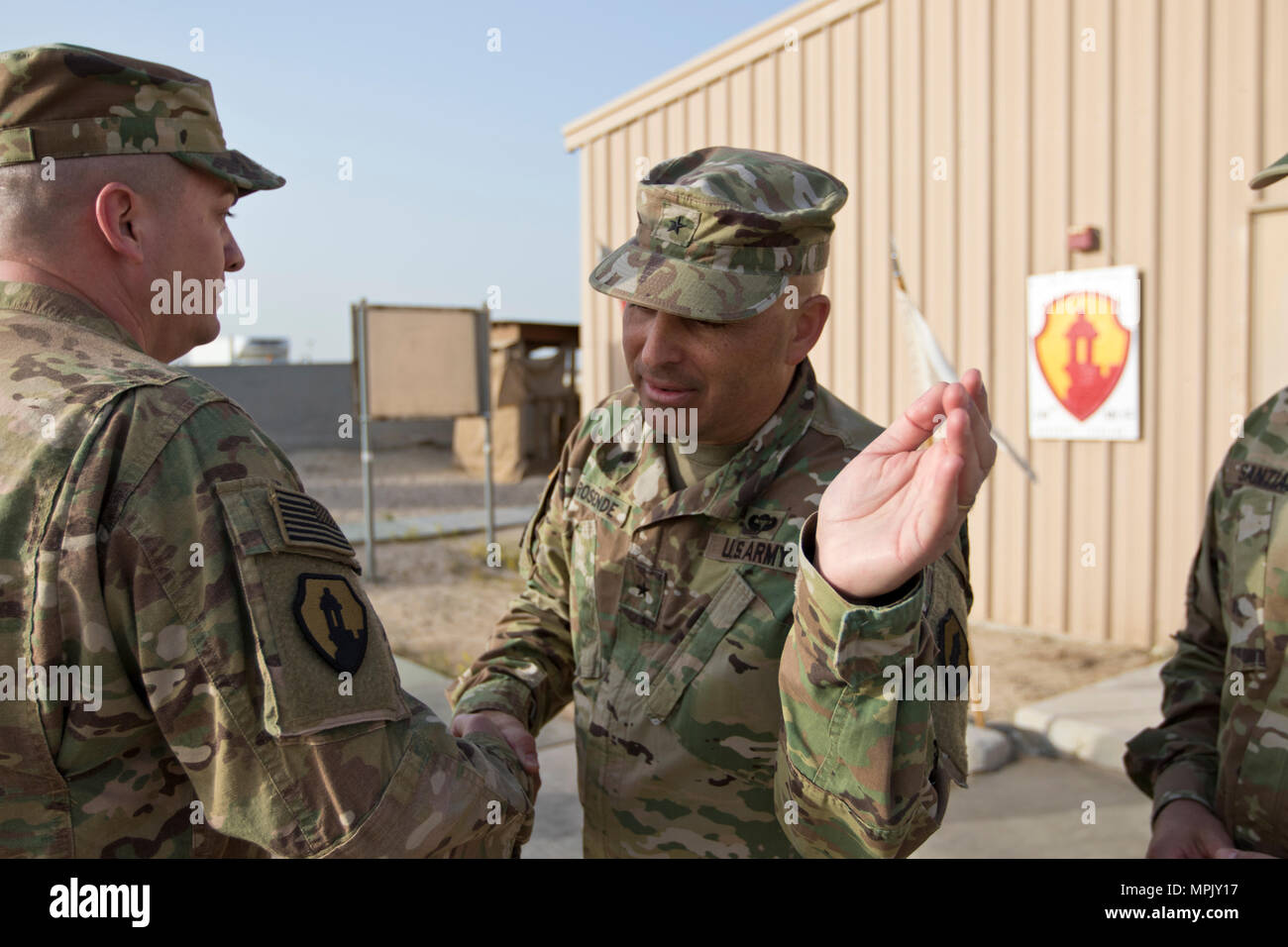 Brig. Gen. Alberto Rosende, commanding general of the 1st Mission Support Command, an Army Reserve unit based out of Fort Buchanan, Puerto Rico, slaps the Garita patch on a Soldier during a patching ceremony for the 246th Quartermaster Company (Mortuary Affairs) at Camp Arifjan, Kuwait, on Mar. 20, 2017. (U.S. Army photo by Staff Sgt. Dalton Smith) - Stock Image
