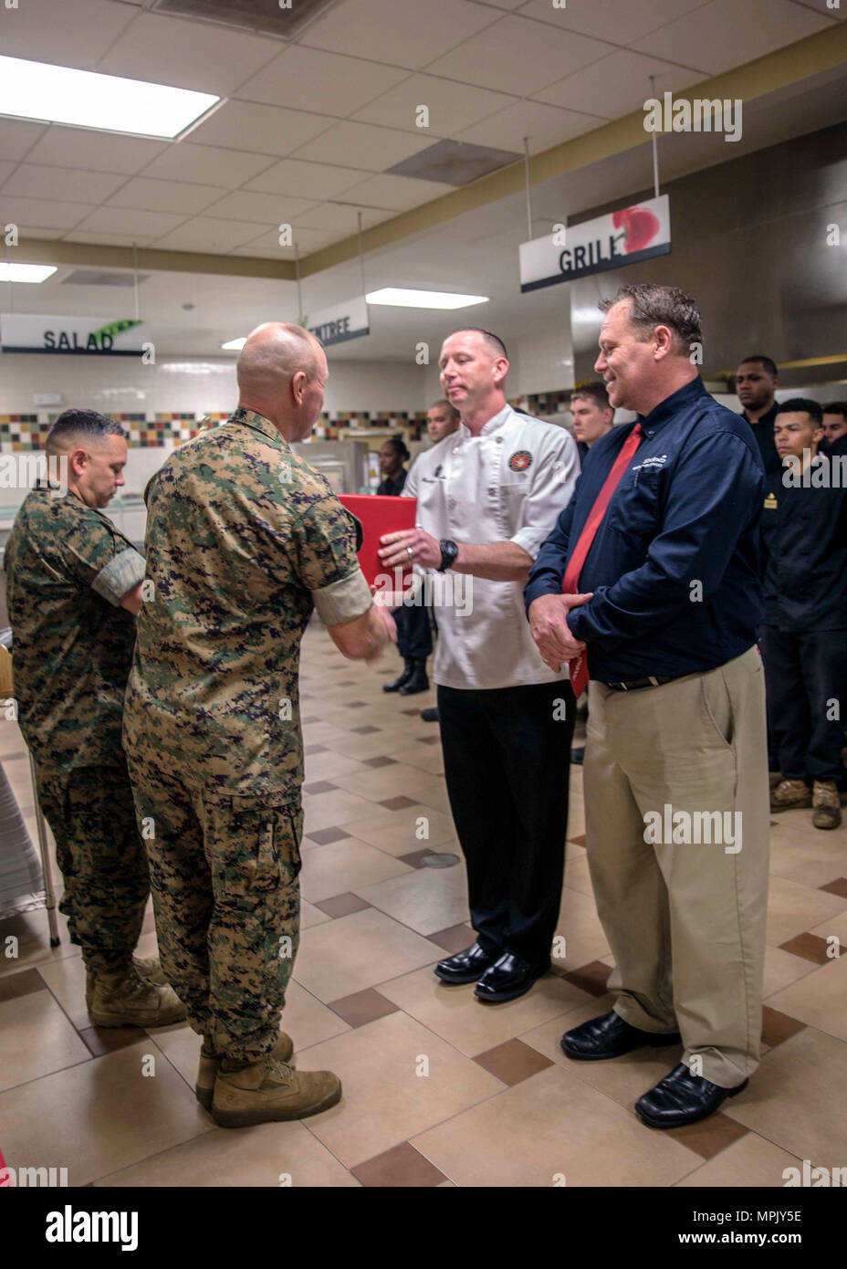 U.S. Marine Corps Col. Scott A. Baldwin, left, assistant chief of staff, Marine Corps Installations Command, presents Master Sgt. Matthew J. Jacobs, regimental mess chief, 2nd Marine Division, with the semiannual Marine and Mess Attendant Award to during an award ceremony for best full food service mess hall in the Marine Corps, Camp Lejeune, N.C., March 14, 2017. The mess halls were judged on factors such as cleanliness, recipe compliance, quality of food, teamwork, execution and training. (U.S. Marine Corps photo by Lance Cpl. Ashley D. Gomez) - Stock Image
