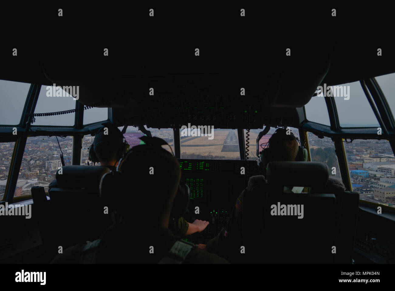 Crew members of the 36th Airlift Squadron approach the runway at Yokota Air Base, Japan, during the first Yokota C-130J Super Hercules training sortie March 20, 2017. The C-130J incorporates state-of-the-art technology to reduce manpower requirements, lower operating and support costs, and provide life-cycle cost savings over earlier C-130 models. (U.S. Air Force photo by Staff Sgt. David Owsianka) - Stock Image