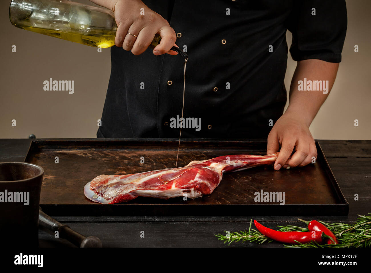 Male chef pouring lamb shank with oil. Chef cooking appetizing shank of lamb. Training, master class, courses - Stock Image