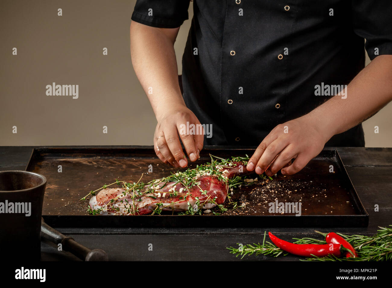 Male chef rubbing raw lamb shanks with greens and spices on stone tray on wooden table. Chef cooking appetizing shank of lamb. Training, master class, - Stock Image