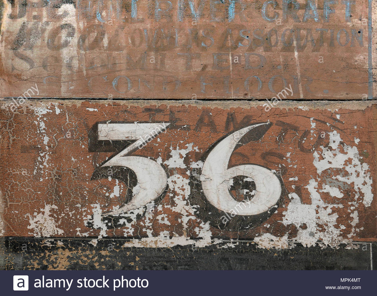 The Number 36 Painted Over Previous Worn And Eroded Lettering On Stone Door  Frame