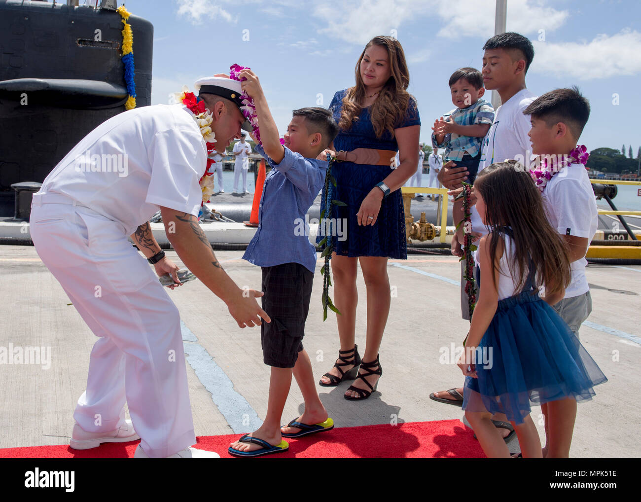 170323-N-LY160-0331 PEARL HARBOR, Hawaii (March 23, 2017) Chief Machinist's Mate (Nuclear) Kalani Eli, a native of Zuni, New Mexico, is greeted by his family on the submarine piers in Joint Base Pearl Harbor-Hickam. The Los Angeles-class fast-attack submarine USS Louisville (SSN 724) successfully completed a six-month deployment to the Western Pacific Ocean. (U.S. Navy photo by Mass Communication Specialist 2nd Class Michael H. Lee/Released) - Stock Image