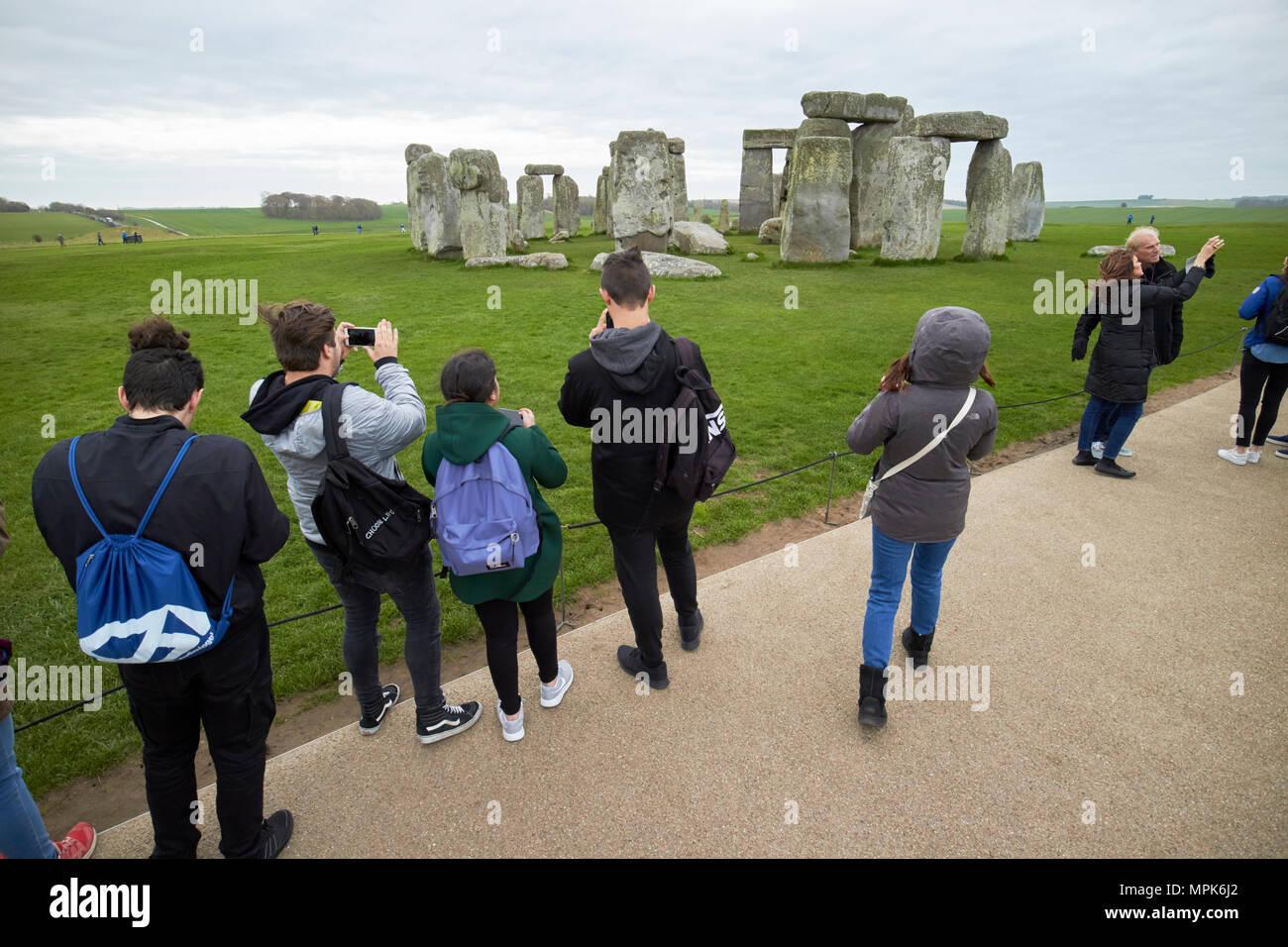 tour group of young students take photos at stonehenge wiltshire england uk - Stock Image