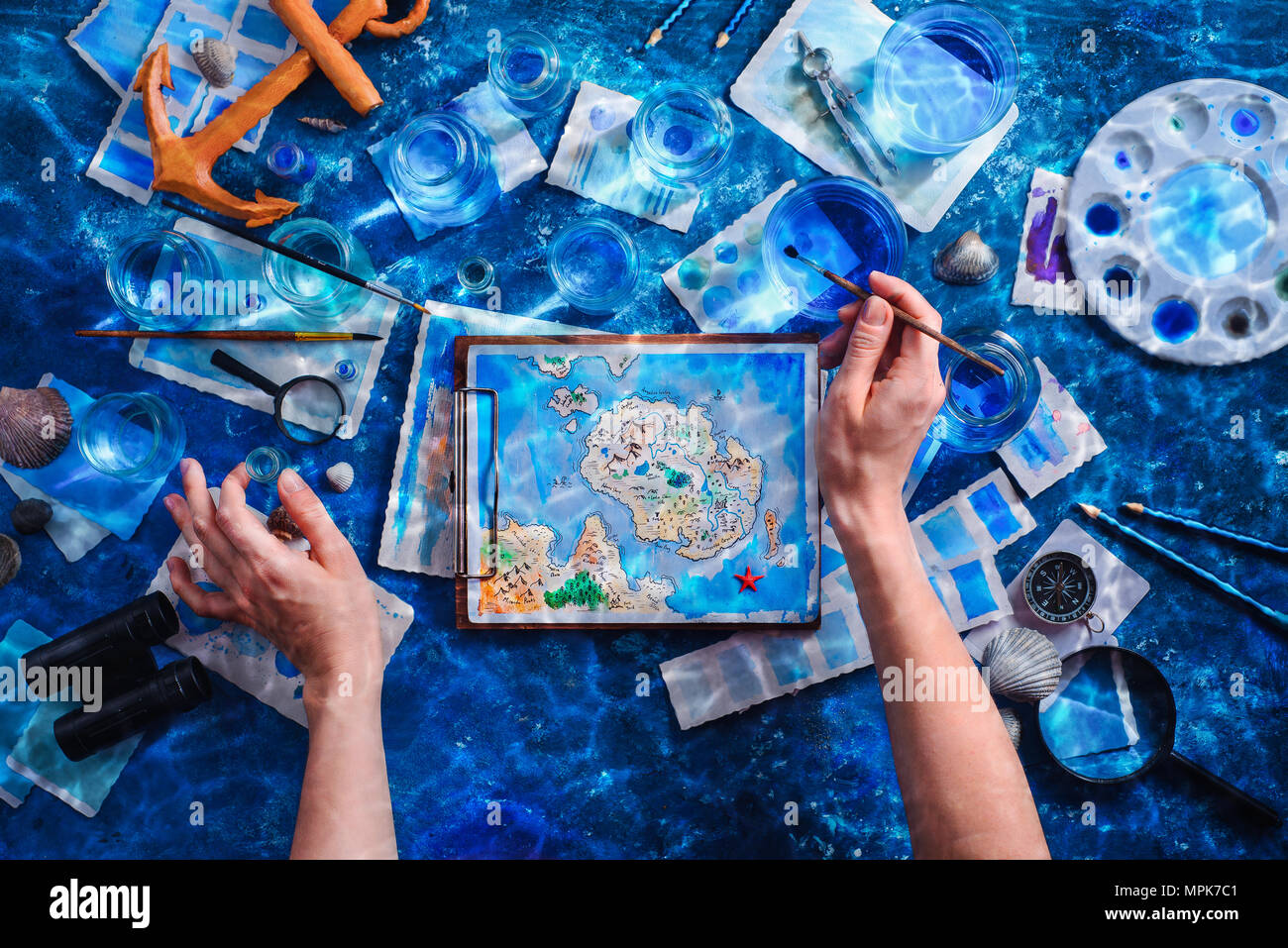 Artist painting a fantasy island map. Underwater still life concept. Creative artist workplace flat lay. - Stock Image
