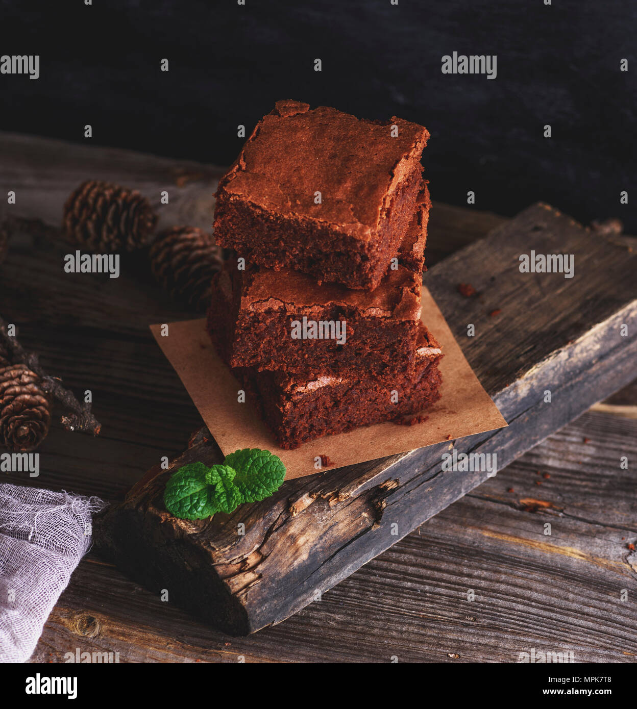 a stack of square pieces of brownie pie on a gray wooden plank, top view - Stock Image