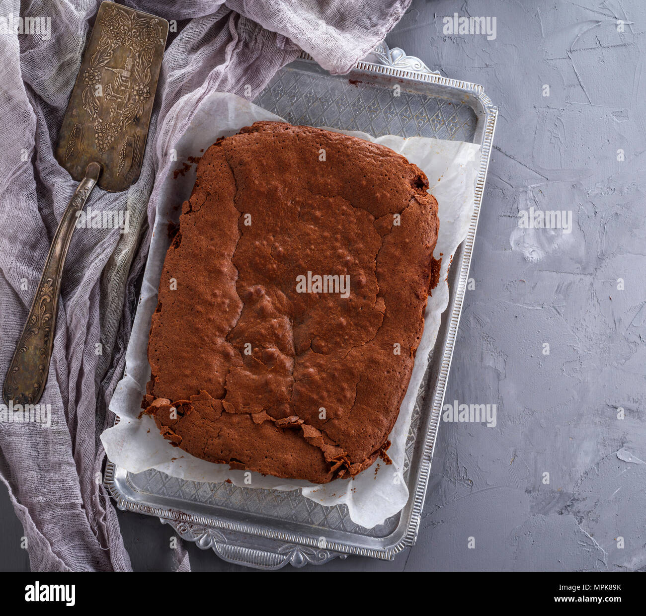 baked chocolate brownie cake on a plate of iron, gray background, view from above - Stock Image