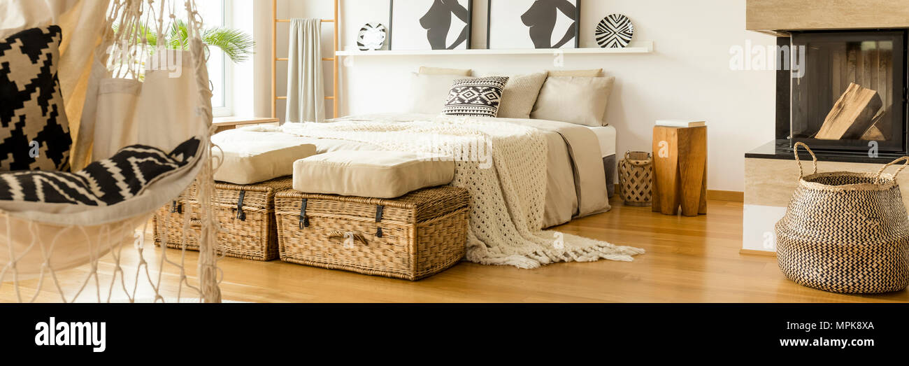 White Knit Blanket Placed On A King Size Bed Standing In Bright Bedroom  Interior With Fireplace, Hammock Chair And Two Straw Baskets