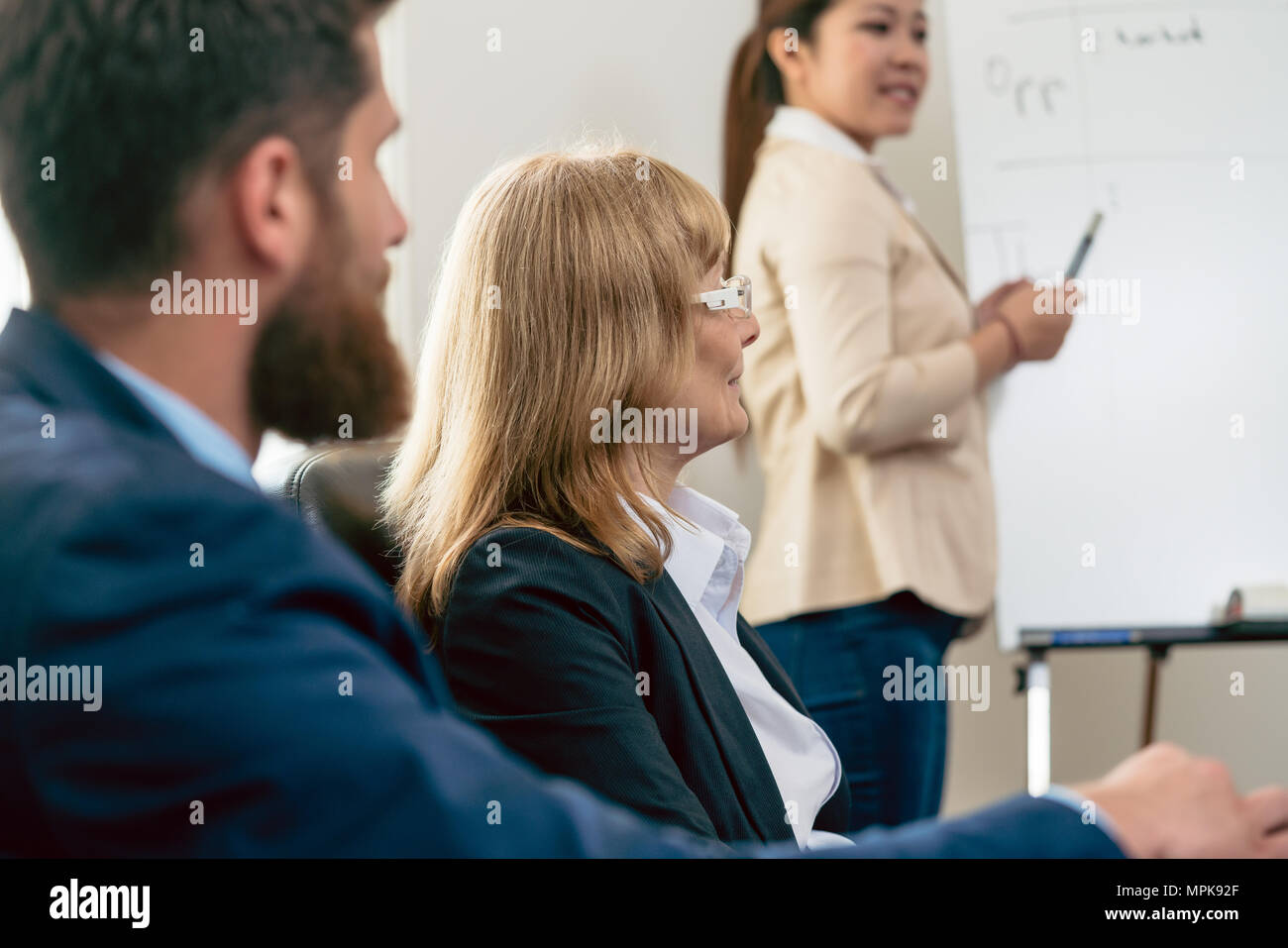 Middle-aged business woman presenting her opinion during a meeting - Stock Image