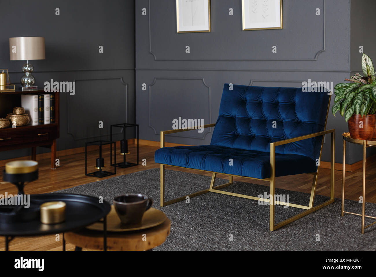 real photo of a large navy blue armchair with golden frame against