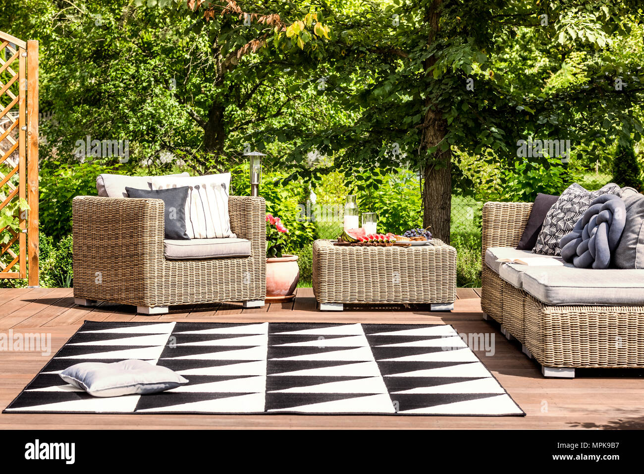 Comfy garden furniture and geometrical rug on a terrace in spa resort - Stock Image
