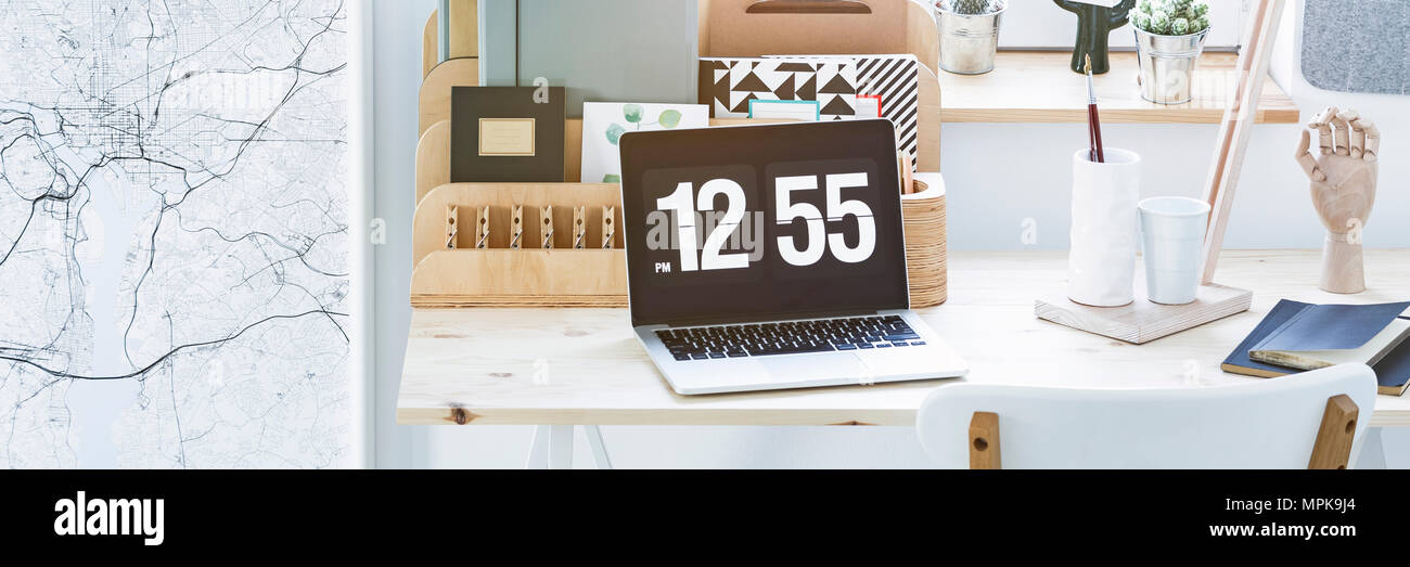 Close-up photo of a laptop with time screensaver placed on home office wooden desk Stock Photo