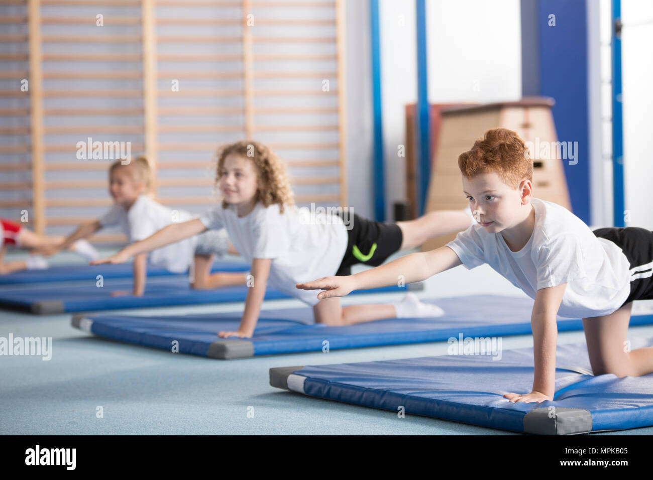 Primary school boy and other kids exercising a balancing table yoga pose during extracurricular gym class to help with posture and core body strength Stock Photo