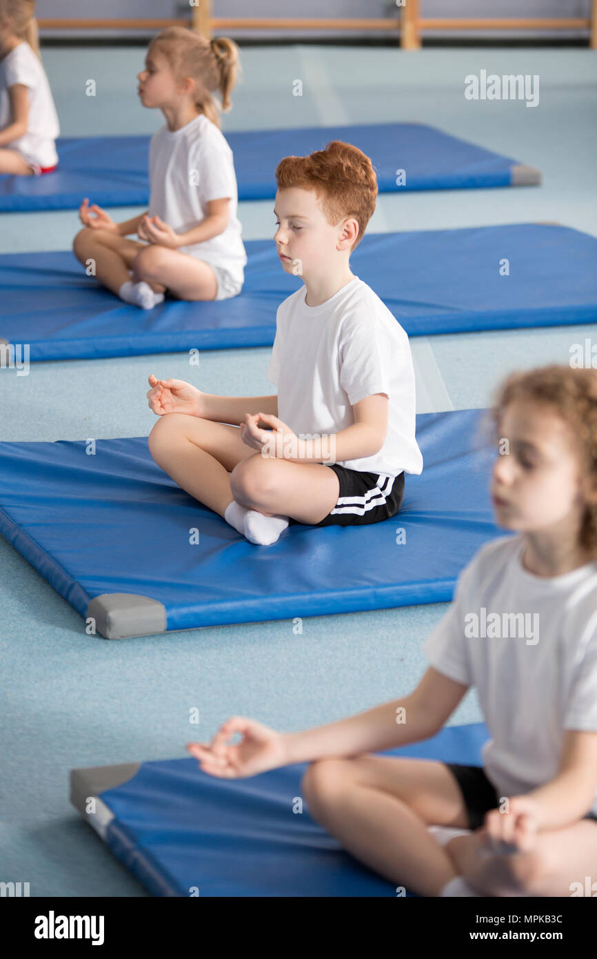 Elementary school pupil and other children sitting on mats with their legs crossed and eyes closed in relaxing meditation class - Stock Image