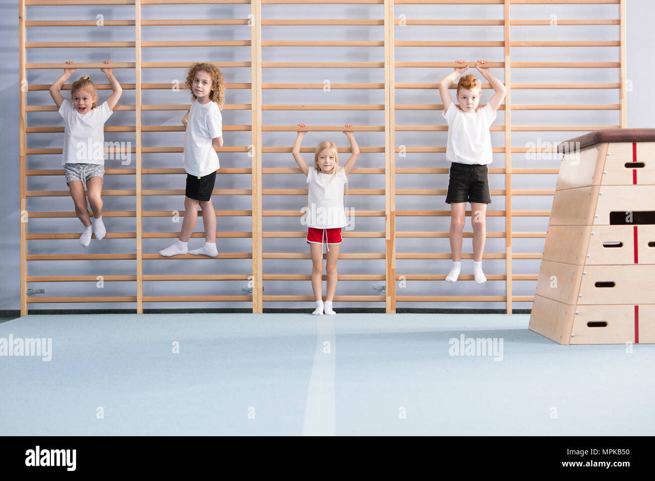 Young, active school boys and girls standing and hanging from wall bars, warming up for physical education athletics class - Stock Image
