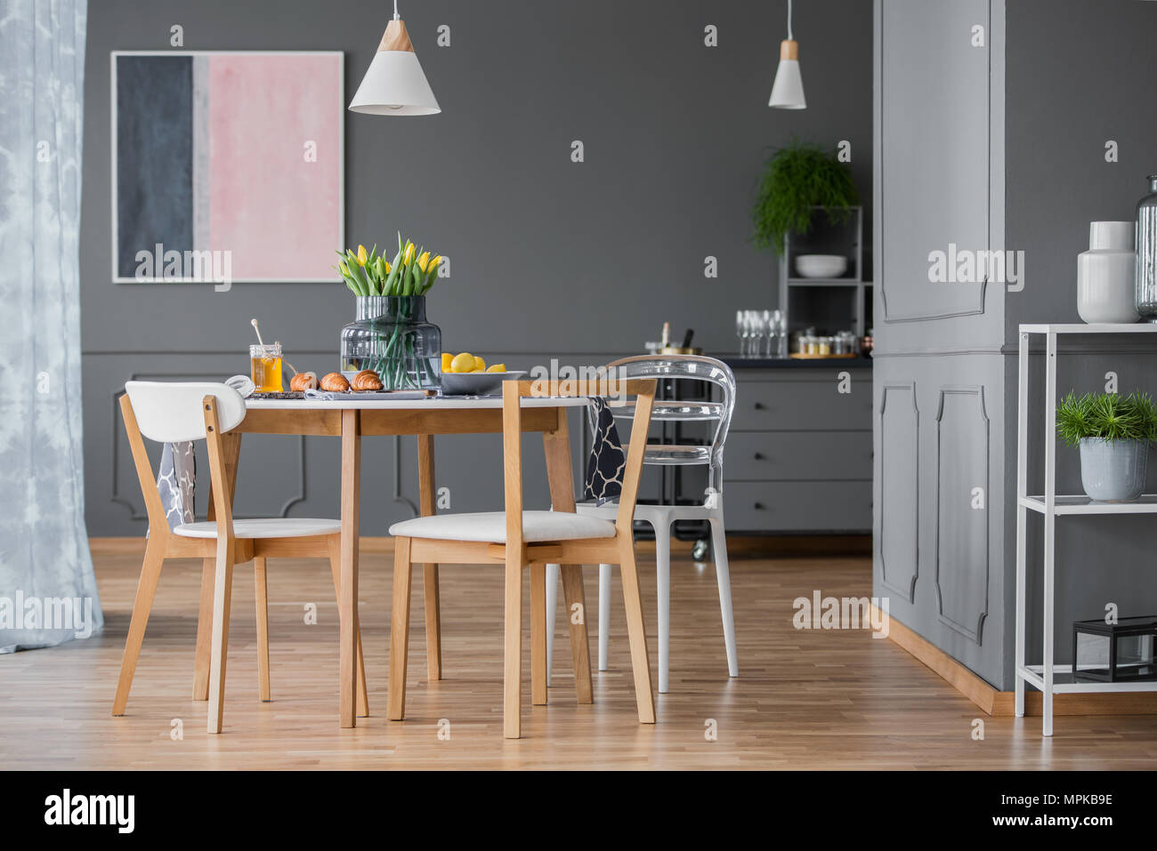 Pink And Navy Blue Painting In Dark Dining Room Interior With Wooden Table  And Chairs